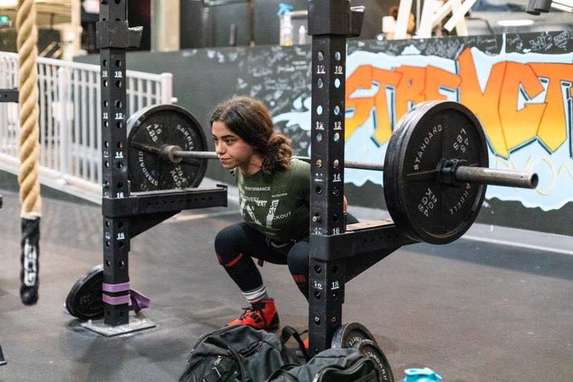 Unleash'd Strength Gym Member Squatting